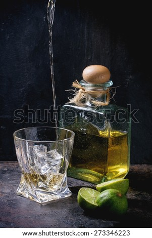 Tequila poured into glass with ice cubes and bottle of tequila, served with sliced limes over black background - stock photo