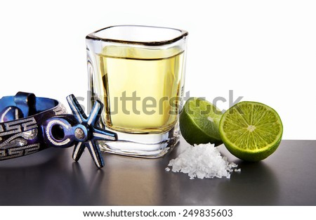 Tequila shot, lemon and salt in a table with spurs - stock photo