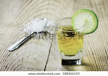 Tequila shot with lime and salt on rustic wooden background - stock photo