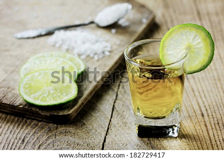 Tequila shot with lime and salt on vintage wooden background - stock photo
