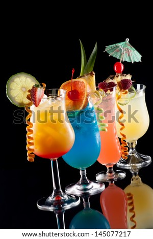 Tequila Sunrise, Blue Lagoon, Rum Runner, and Bahama Mama cocktails over black background on reflection surface, garnished with strawberry, lime, pineapple flag, fresh raspberry - stock photo