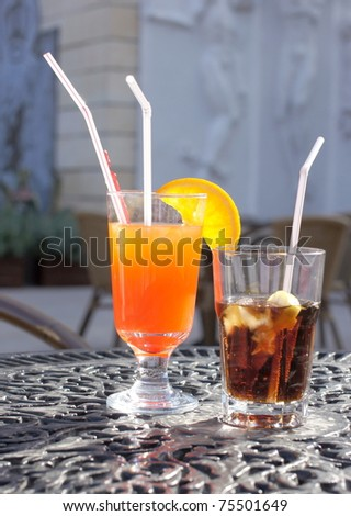 Tequila Sunrise cocktail and a cool cola drink served  on a terrace - stock photo