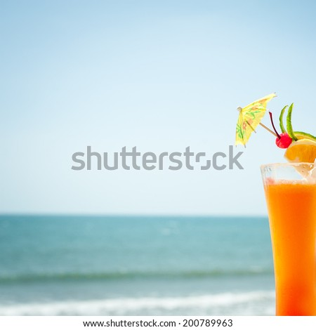 Tequila sunrise cocktail fruits and umbrella decoration at tropical ocean beach. Vintage style, hipster colors image with copy space for party invitation text  - stock photo