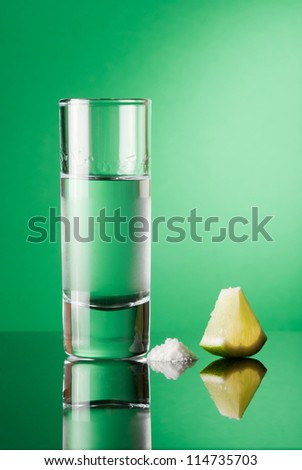 Tequila with lime and salt on a green background - stock photo