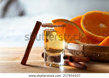 tequila with orange and cinnamon on a wooden table - stock photo