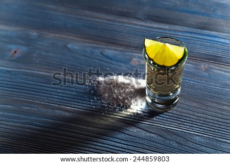 tequila with salt and lime on old wooden table - stock photo