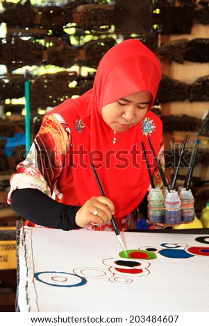 TERENGGANU, MALAYSIA - APRIL 16,2014 - An artist carefully trace on a traditional batik at Noor Arfa Craft Complex, Terengganu, Malaysia - stock photo