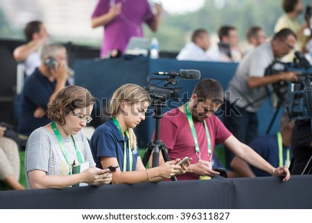 Teresopolis, Brazil - March 22, 2016: journalist group working on coverage of the Brazilian soccer team with a cell phone at hand - stock photo
