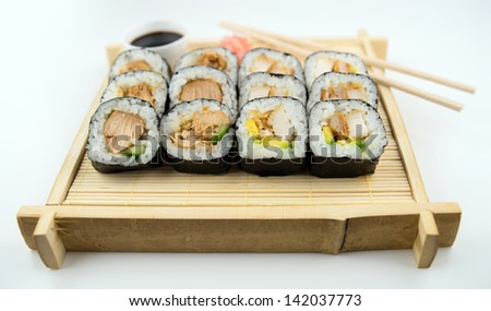 Teriyaki and fried chicken sushi rolls on Japanese bamboo mat with chopsticks, soy sauce and ginger - stock photo