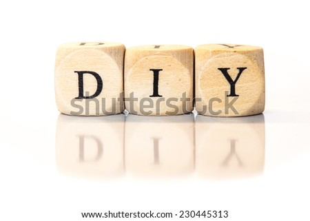 Term DIY spelled from toy cubes, dice letters with reflection on bottom. Studio shot on White background. - stock photo