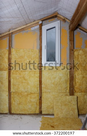 termal insulation installing at the attic - stock photo