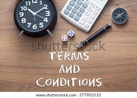 Terms and conditions written on wooden table with clock,dice,calculator pen and compass - stock photo