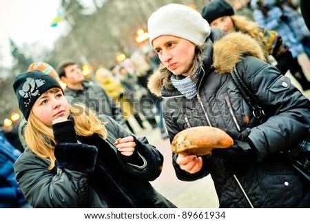 TERNOPIL, UKRAINE - NOVEMBER 26: Unidentified people sharing bread at Ukrainian Holodomor Memorial Day on November 26, 2011 in Ternopil, Ukraine - stock photo