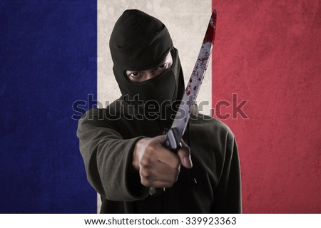 Terorrism concept: terrorist threatening with a knife in front of France national flag - stock photo