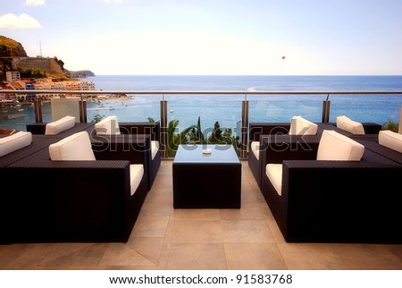 Terrace lounge with rattan armchairs and seaview in a luxury resort . - stock photo