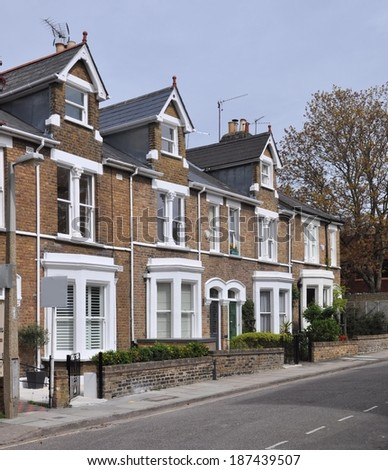 Terrace of 19th century English Victorian period town houses, with blank sales signboard. - stock photo