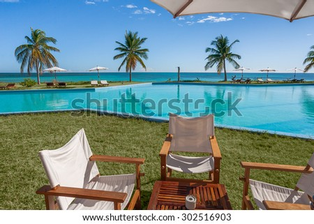 Terrace on the lawn in front of the pool and the sea - stock photo