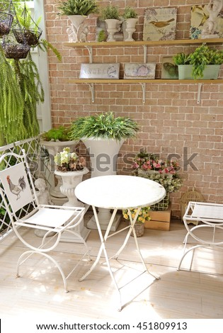 terrace or balcony with small table, chair and flowers - stock photo