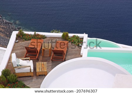Terrace with deck chairs and a water pool. View to the sea in Santorini island, Greece - stock photo