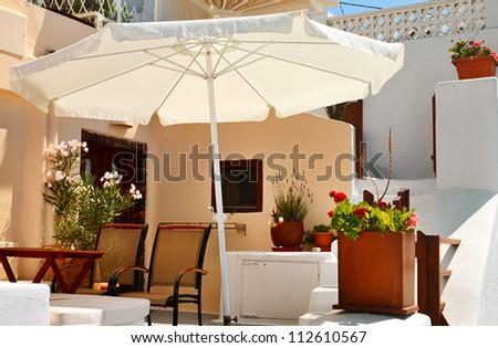 Terrace with sunshade  decorated  flowers on Santorini, Greece. - stock photo