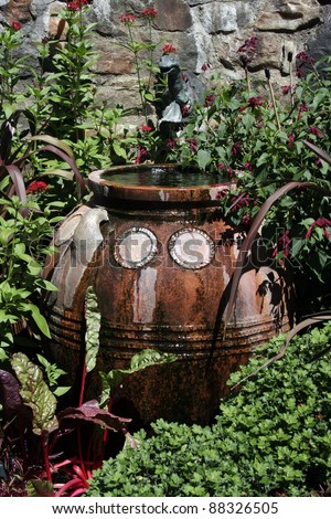 terracotta water container in lush garden - stock photo