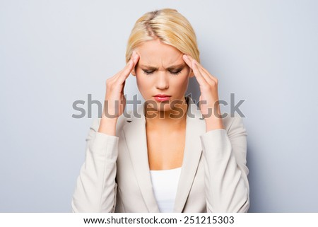 Terrible headache. Depressed young businesswoman touching her cheekbone and keeping eyes closed while standing against grey background - stock photo
