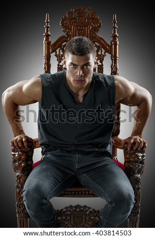 Terrible muscular man rises from his throne - stock photo