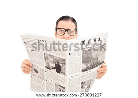 Terrified man holding a newspaper. The newspaper is custom made and the pictures are my copyright.  - stock photo
