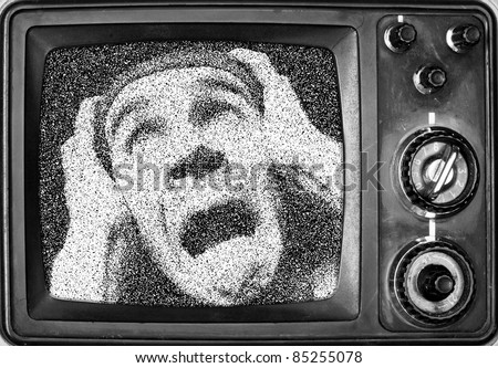 Terrified man on screen of vintage TV. Horror concept - stock photo