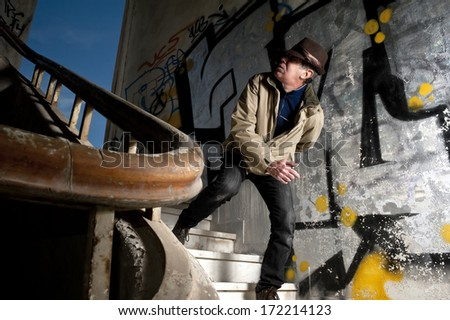 Terrified man walking down the stairs in a strange building  - stock photo