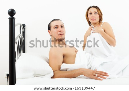 Terrified middle-aged couple caught during adultery - stock photo
