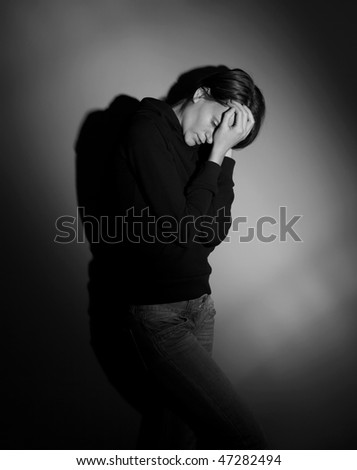 terrified/scared young woman subject to domestic violence - stock photo