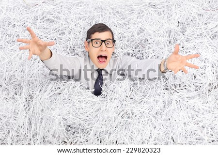 Terrified young man drowning in a pile of shredded paper  - stock photo