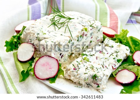 Terrine of cottage cheese and radish with dill, chives, salad in white plate, napkin on a light wooden planks - stock photo