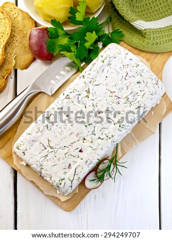 Terrine of curd and radish with dill, chives, knife on paper and board, bread, boiled potatoes, napkin, parsley on a light wooden planks - stock photo