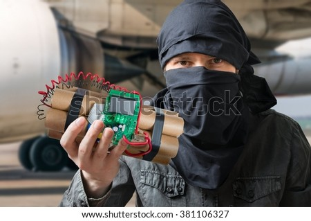 Terrorism concept. Terrorist in airport holds dynamite bomb in hand. - stock photo