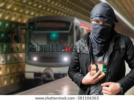 Terrorist has dynamite bomb in jacket. Train approaching underground station. Terrorism concept. - stock photo