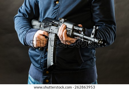 terrorist holding kalashnikov rifle isolated on a black background - stock photo