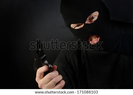 terrorist in a ski mask holding a gun with a dark background - stock photo
