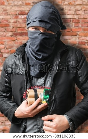 Terrorist puts dynamite bomb in jacket. Terrorism concept. - stock photo