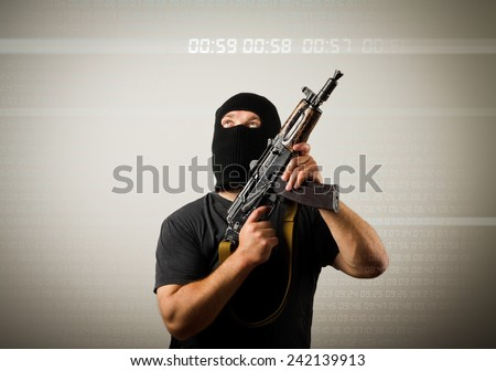 Terrorist with gun looking at a digital clock. Time concept. - stock photo