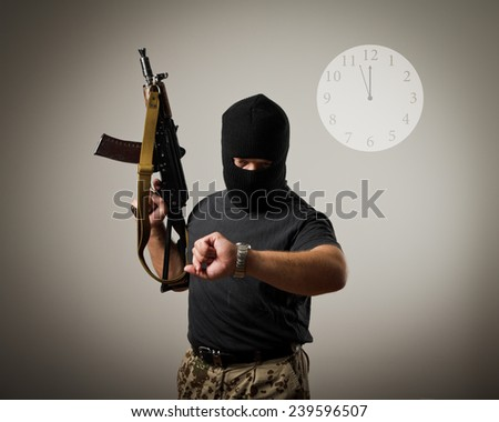 Terrorist with gun looking at his wristwatch. Time concept. - stock photo