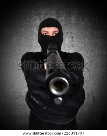 terrorist with gun on black wall background - stock photo