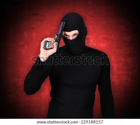 terrorist with gun on red wall background - stock photo