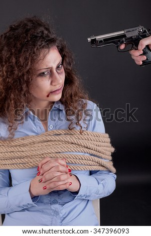 terrorists holding a gun to a woman's head - stock photo