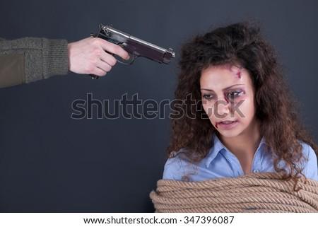 terrorists threatening the a frightened girl with gun - stock photo