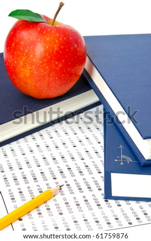 Test score sheet with answers, book and apples - stock photo