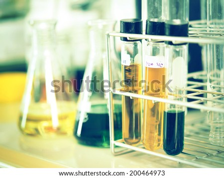 Test tube in a rack with flask containing chemical liquid - stock photo