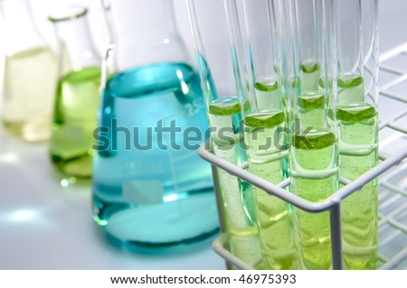 test tubes and flasks with green and blue liquid in a laboratory - stock photo