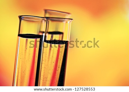 Test tubes on a yellow background. Small depth of field. - stock photo